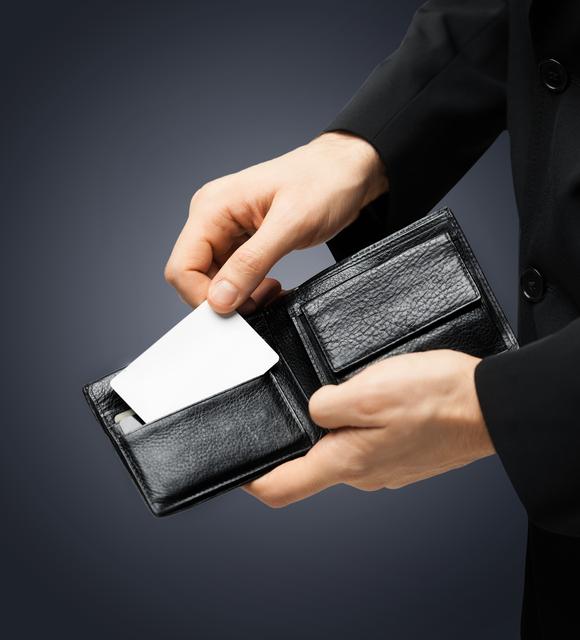 財布からカードを出すスーツ姿の男性の手元