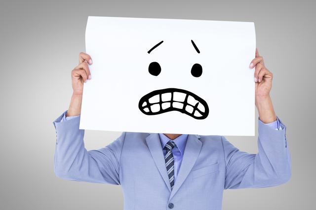 困り顔のイラストを顔の前に持っている人