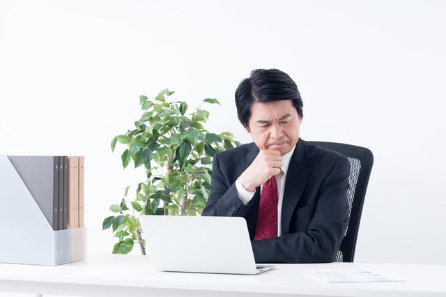 パソコンの前で悩むスーツ姿の初老男性
