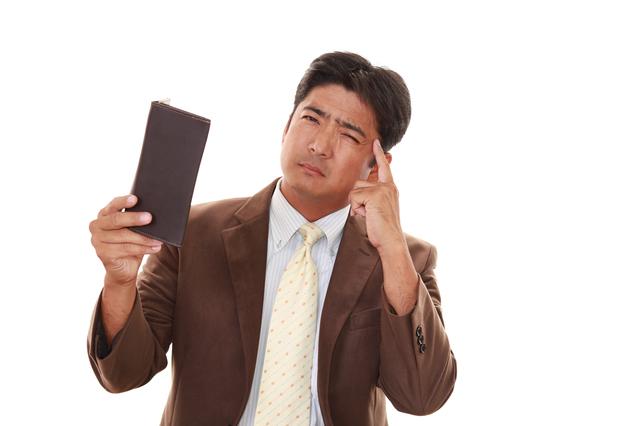 財布を持って悩む茶色いスーツ姿の男性