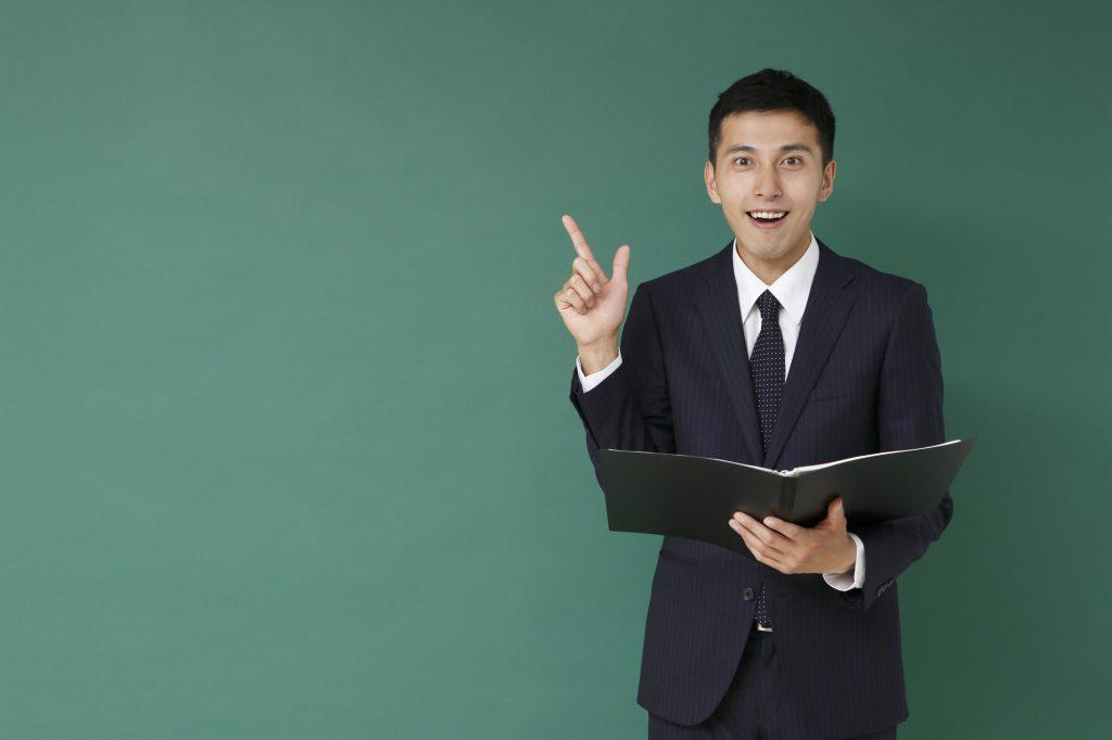 右手を上げているスーツ姿の男性