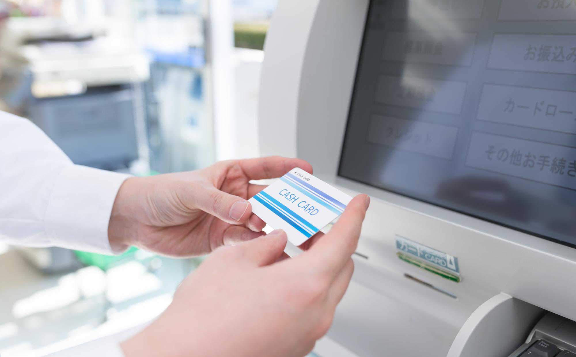 ATMで振込返済する男性