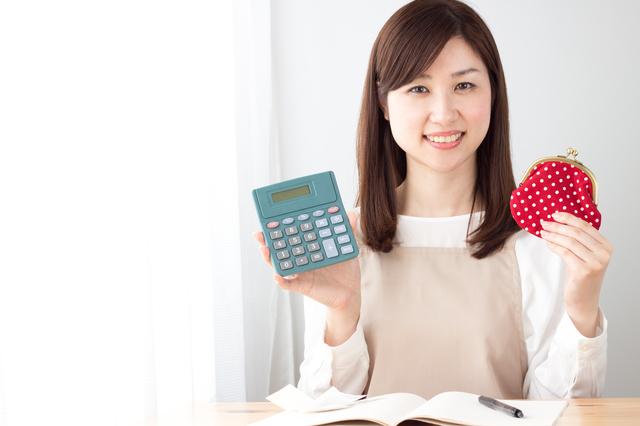 電卓と財布を持っているエプロン姿の女性