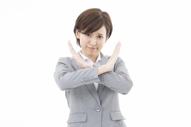 バツ印をつくる女性